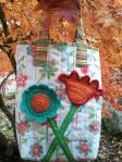 Happy tote bag with crocheted flower applique motifs