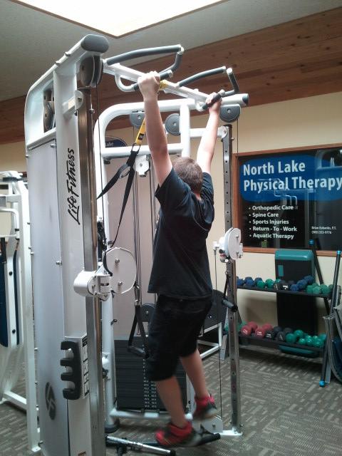 Ben hanging on workout equipment