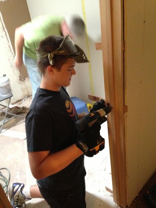 Dylan putting in door hardware in his bedroom